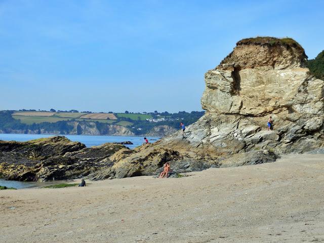 The rocks and beach with holiday makers at Carlyon Bay, Cornwall