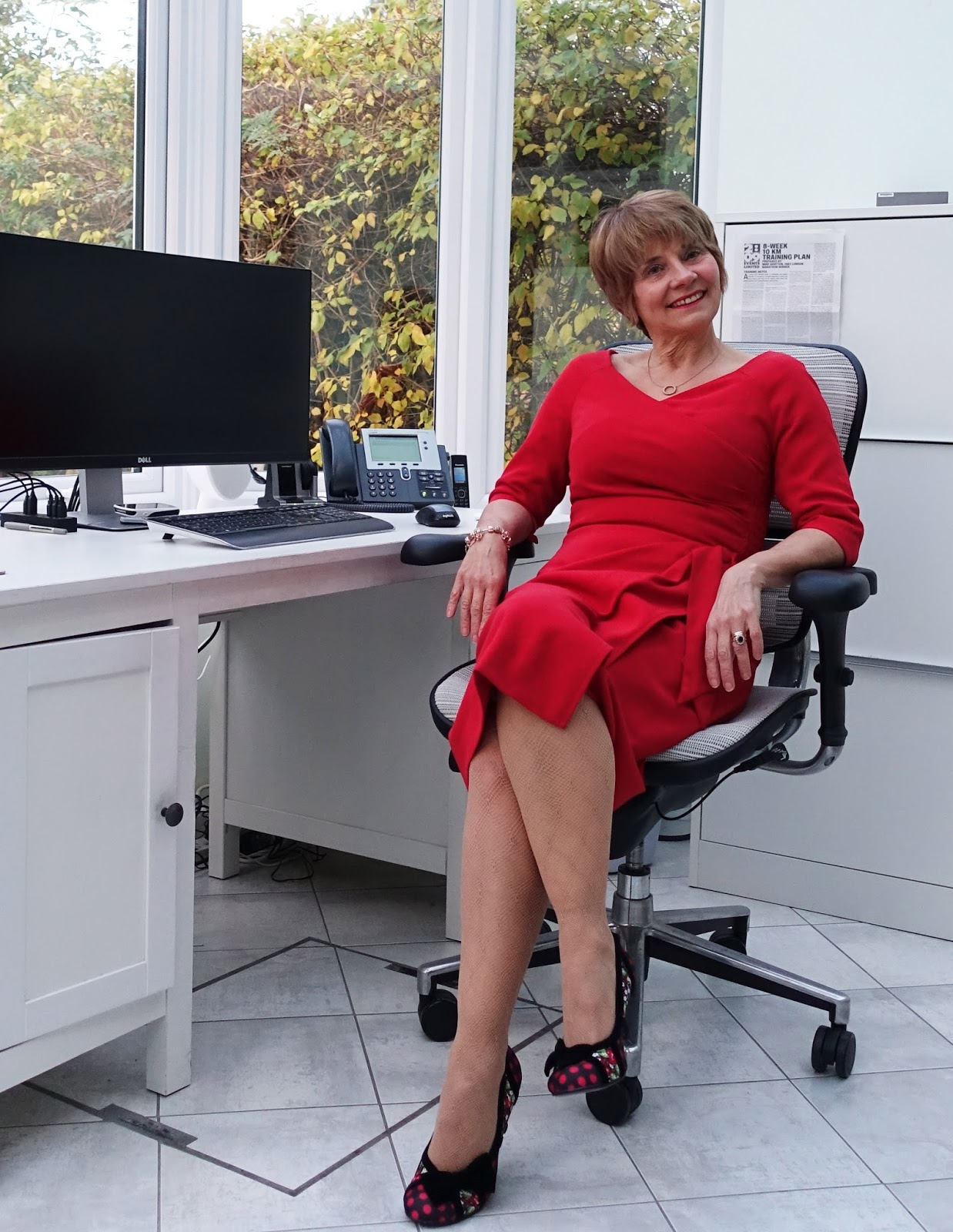 Image showing a 50 plus woman in a white conservatory wearing a red Bombshell dress, nude fishnet tights and red and black Poetic Licence shoes