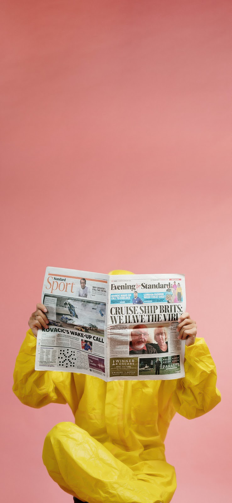person in yellow coveralls reading newspaper wallpaper