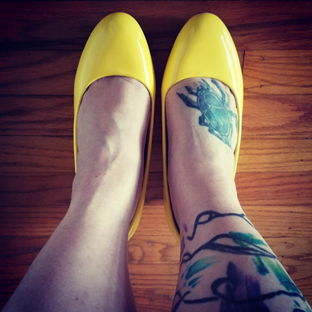 image of my bare tattooed legs from mid-calf down, with my feet wearing yellow patent shoes