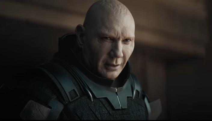 Imagem: o personagem Glossu, interpretado por Davi Baustista, um homem careca, pálido com olhos escuros e usando uma armadura de couro e metálico observando algo.