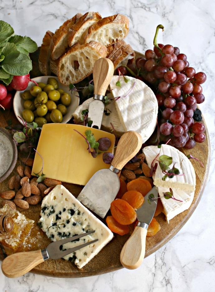 Cheese board with an array of French hard and soft cheeses, baguettes and edible flowers.