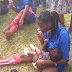 Female football player seen breastfeeding her baby during a half time in Akwa-Ibom state