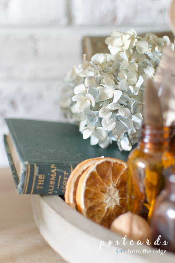old book, dried oranges and hydrangeas, amber bottles and fall decor on tiered tray for fall