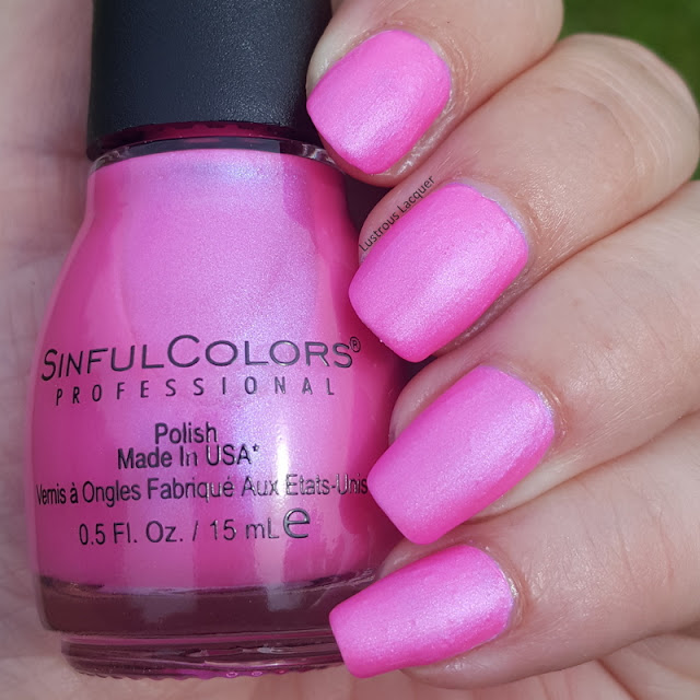 Bright bubblegum pink neon nail polish with blue shimmer in a matte finish