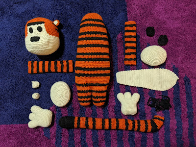 A flat lay of the parts of crochet Hobbes (tiger) plushie, where all the body parts are laid out before construction. They are on a purple and blue geometric carpet.