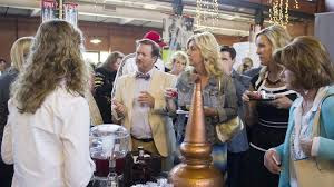 many bystanders standing around a table sampling food and beverages at the taste of the highlands