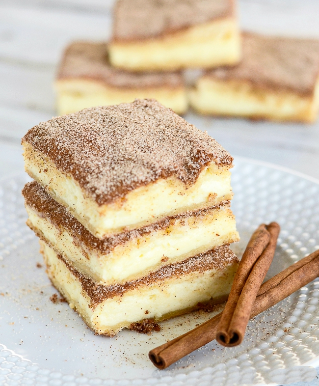 Churro Cheesecake Bars - The crunchy cinnamony goodness of a churro filled with a tangy cream cheese filling. The best of two desserts rolled into one!