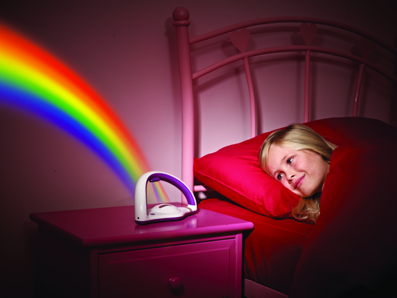 A girl lying in bed looking at a rainbow projected on to the wall