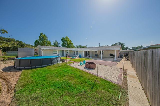 Foto ilustração que mostra duas casa em um terreno grande com piscina azul de lona e uma gramado.