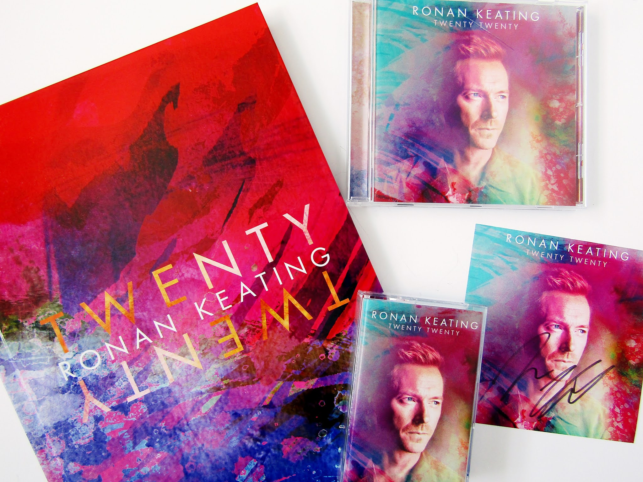 A flatlay photo taken from above of various Ronan Keating Twenty Twenty albums. The photo shows an A4 photo book collector's album, a CD, cassette tape, and a signed card featuring a purple, blue, and red design, the words 'Ronan Keating Twenty Twenty' in gold,  and Ronan Keating's face on them.