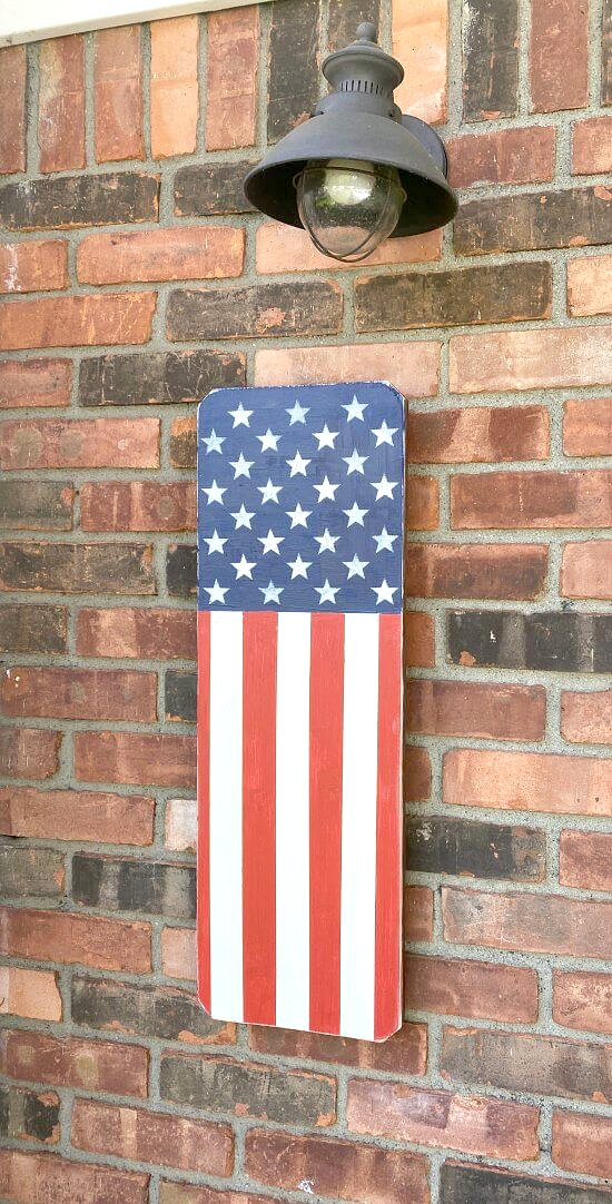 Wooden American flag hanging on brick wall