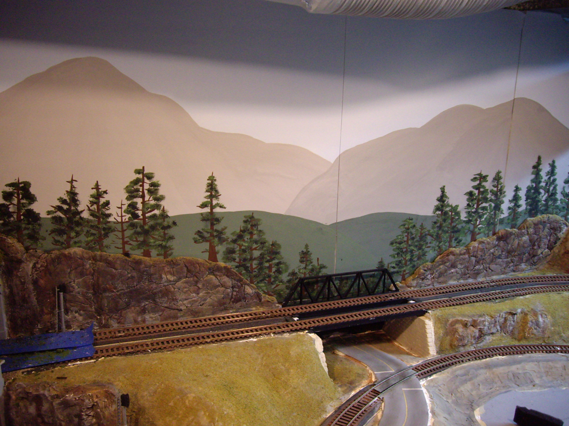 Partially completed model railroad backdrop scenery and surrounding terrain