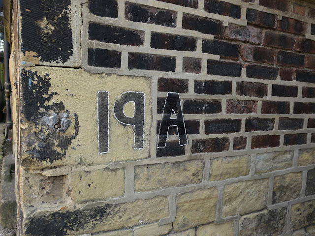 Sign. '19A' written on sooty stone building.