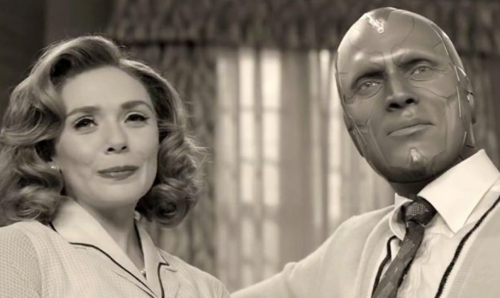 Imagem de capa: Wanda Maximoff, a Feiticeira Escarlate e o Visão, numa foto em preto e branco, vestidos com roupas de época da década de 30, como que saídos de uma sitcom americana antiga.