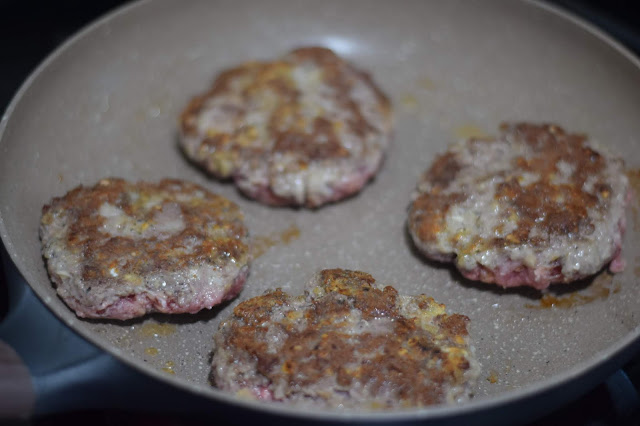 The four salisbury steak patties brown in a skillet.