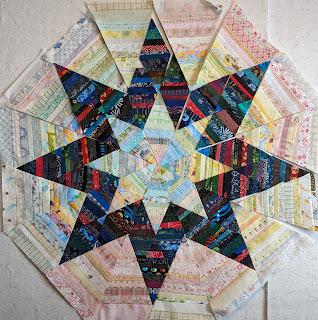 Sixteen large, light value isosceles triangles form an octagon around the dark string diamonds.