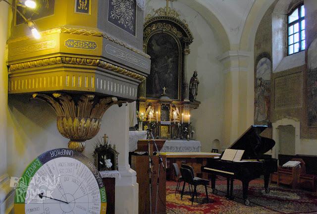 Barokk templombelső, balra szószék, középen pedig egy zongora, háttérben az oltár.