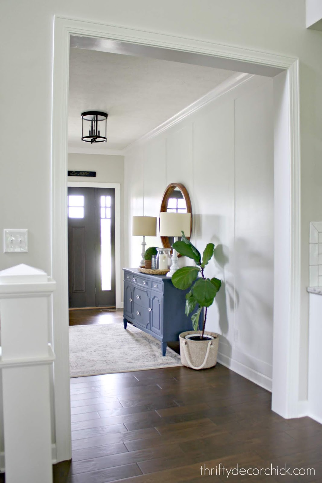 White accent wall in foyer with wood