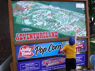 a boy points at a map of Adventureland Park in Altoona, Iowa