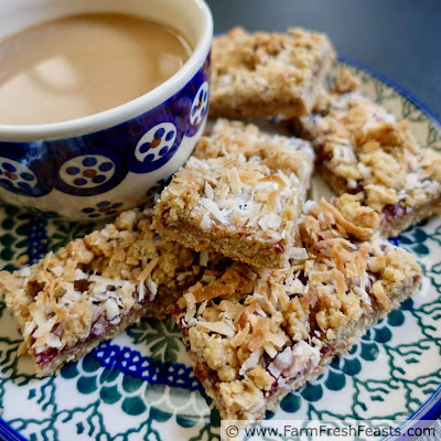 close up image of oatmeal coconut raspberry jam bar cookies on a plate