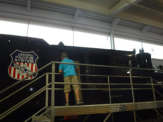 a boy in a blue shirt peers inside the window of a large black steam engine with the Union Pacific logo on it from a platform at the Durham Museum