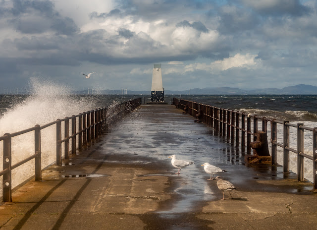 Photo of spray being blown across the pier at Maryport by high winds