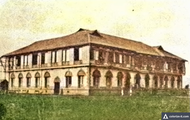 "A school building in Batangas town early during the American colonial era.  Image from the public domain publication ""A Tribute of Love to the Memory of Anna \Elizabeth Hahn.""  Colorized courtesy of Algorithmia."