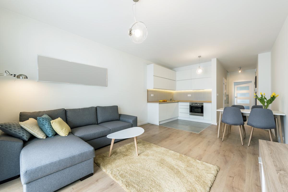 Salón con paredes blancas y espejo sobre el sofá con chaise longue