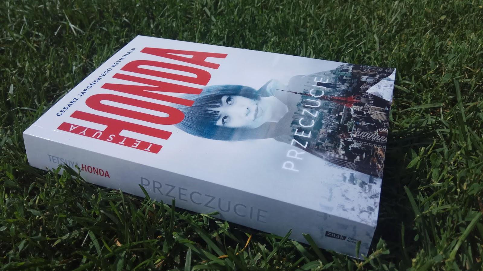 Przeczucie, autor Tetsuya Honda - okładka książki na tle trawy