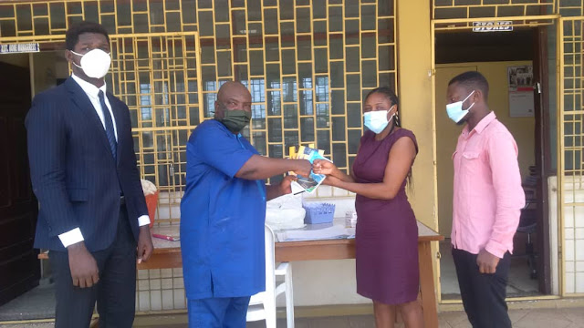 Mr. Kuranchie presenting samples of the two books to an official of the Osu Children's Home. On the right is Mr. Prince Fosu, Head of Marketing and Sales, Swift Group of Companies, with Mr. William Kuranchie looking on.