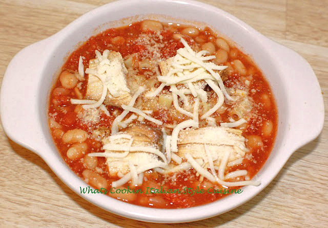 this is a bowl of pasta fagioli in a white dish topped with mozzarella and grated cheese. This pasta fagioli has chicken cubes in it and beans.