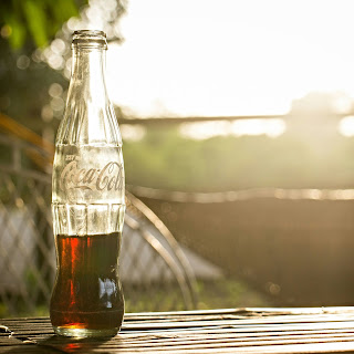 Half empty bottle of Coca-Cola sitting on a table.