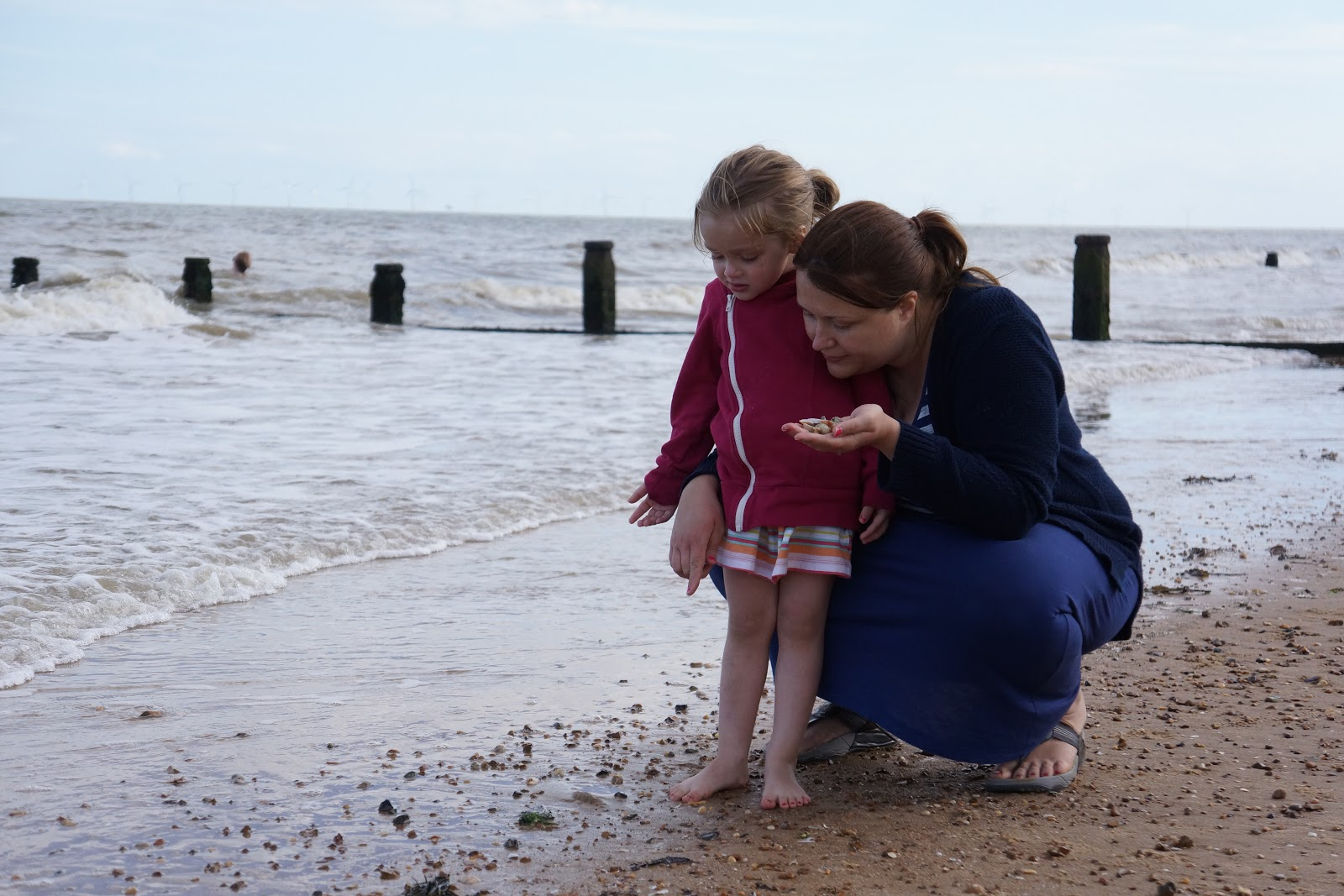mum collecting seashells with daughter