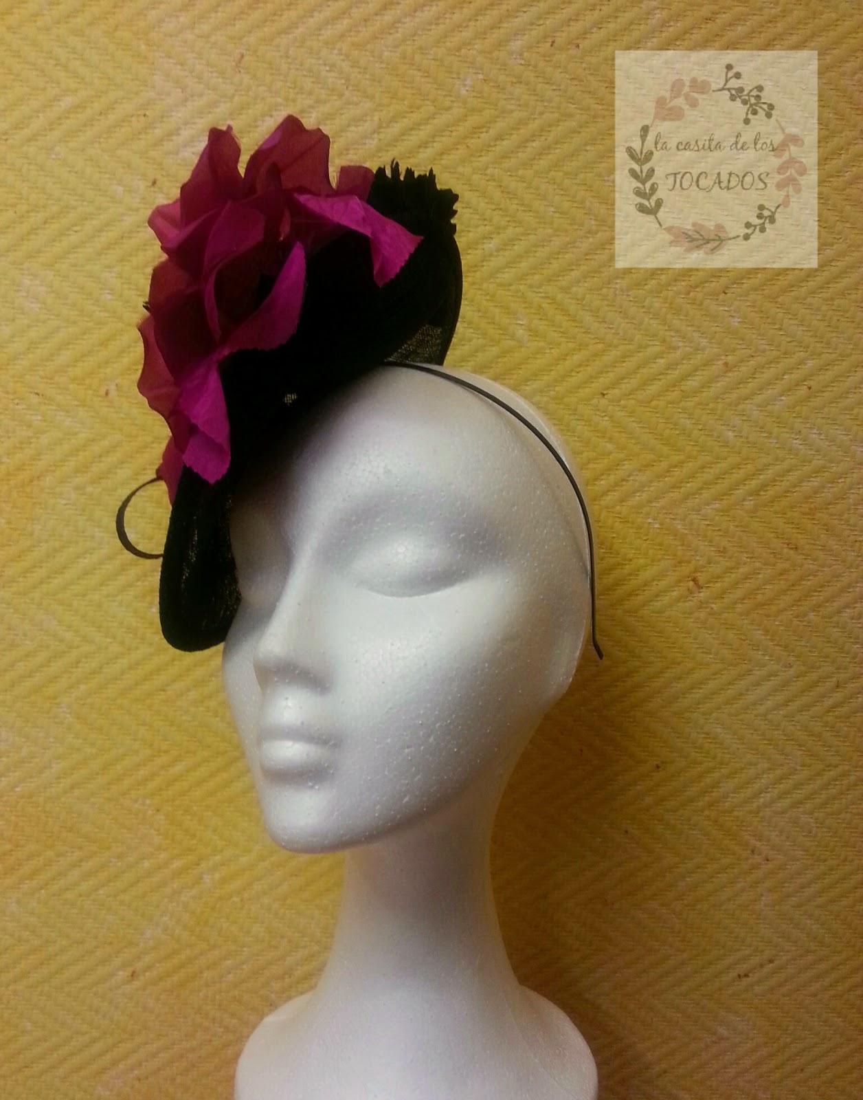 tocado elegante para boda con base negra, adornos y flor de clavel en negro y flor grande en fucsia