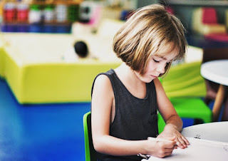 A child drawing in a classroom