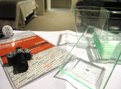 A conference lanyard on a desk in a hotel room. On it is a miniature camera, and next to it are a number of clear plastic containers which look like miniature planters and sinks.