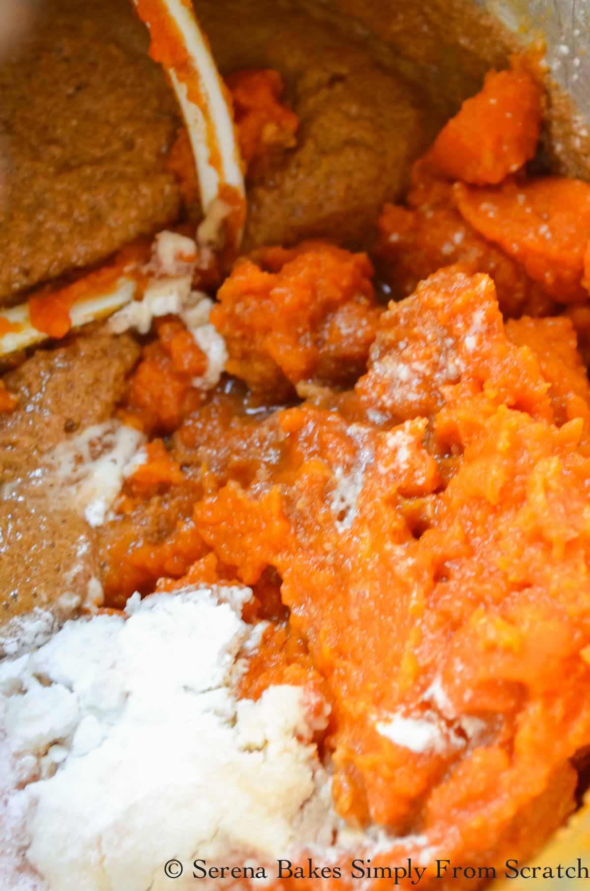 Pumpkin Puree, Baking Powder, Baking Soda, and Salt added to Pumpkin Bread batter in a stainless steel mixing bowl.