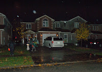 A rainy halloween night in a residential neighbourhood.