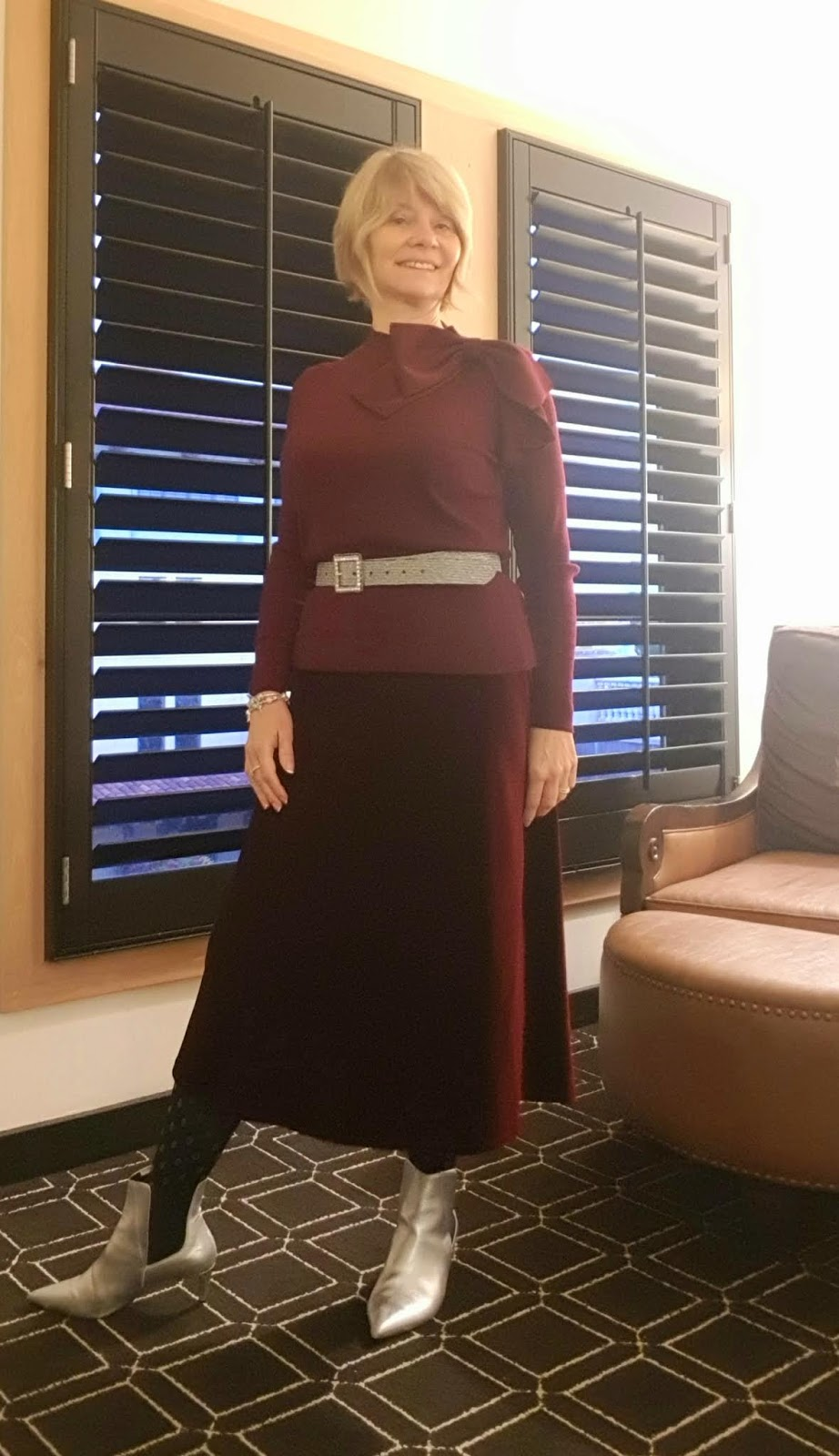 Gail Hanlon, over 50s style blogger, in monochrome burgundy: velvet skirt and top worn with a silver belt and silver ankle boots to add some originality.