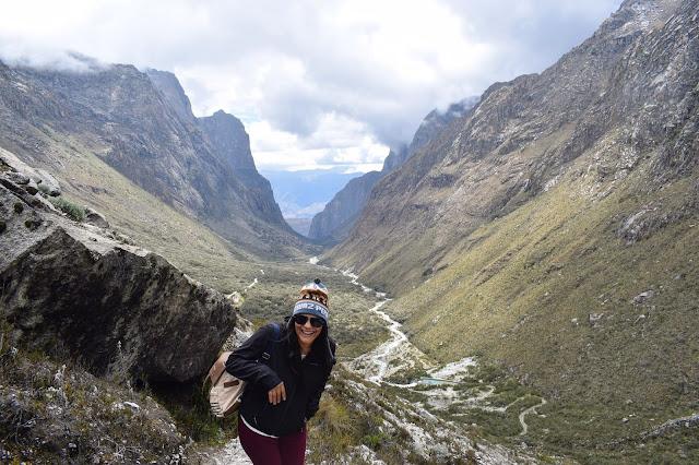 mulher de touca e mochila em um trekking