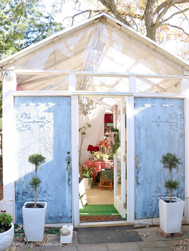 Salvaged vintage doors from San Diego were repurposed as the west wall with French Country style in a green house.