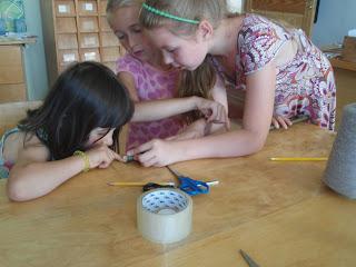 Nuotraukoje trys mergaitės Labardžių bibliotekoje gamina aitvarą.