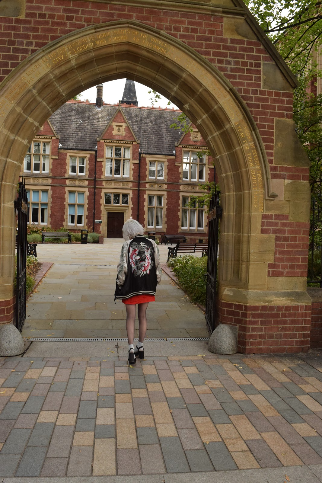 silver haired girl wearing heels, red dress and souvenir jacket standing in an archway at Leeds uni