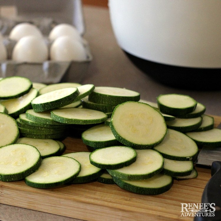 Prepping for zucchini appetizer with sliced zucchini on cutting board and carton of eggs in background