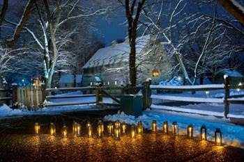 Two story wooden building in the background with snow on the ground and in the trees. A dozen lanterns are lighted and in a row in the front of the image.