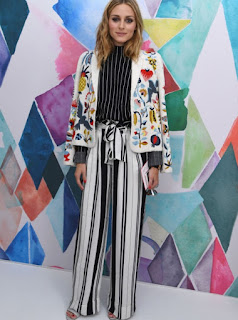 Olivia Palermo at Schiaparelli Haute Couture 2016/17 show in a black and white stripe long sleeve top and wide leg trousers and a white embroidered long sleeve jacket