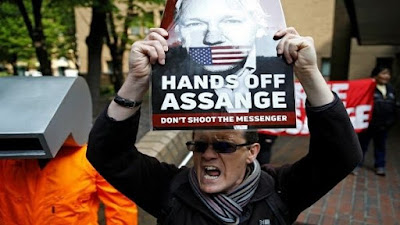 Homem com cartaz pedindo Assange livre