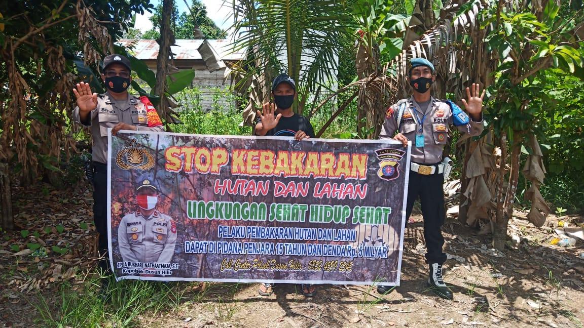 Sosialisasikan Isi Spanduk, Personel Polsek Dushil Ajak Masyarakat Cegah Karhutla