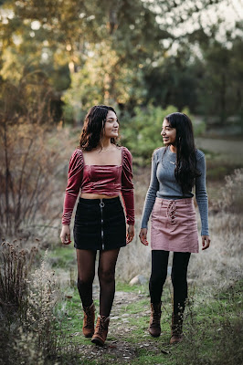 Teenage sisters walking holding hands posing for Christmas mini sessions with Morning Owl Fine Art Photography located in San Diego.